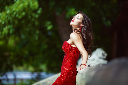 Chic woman with dark curly long hair in red dress