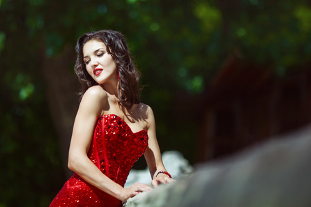 attractive girl with curly long hair in red dress