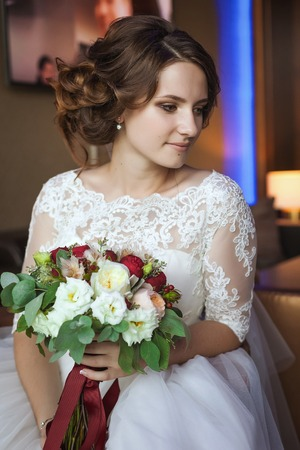 wedding feast: Young and beautiful bride with flower bouquet in hotel Stock Photo