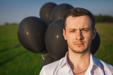 Man in white shirt with black balloons in field