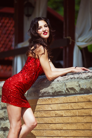 attractive curvy brunette in red stone dress with sexy body