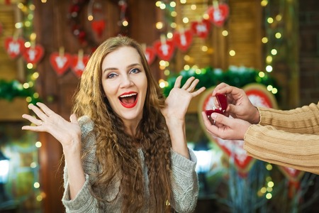 Surprised blonde girl takes gift ring in red box Stock Photo