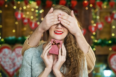 Man surprising his delighted girlfriend with purple square box Stock Photo