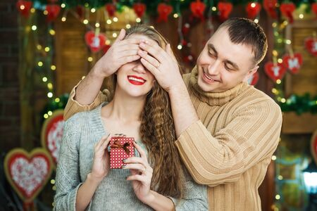 Man keeps his girlfriend eyes covered while she giving gift, romantic surprise for valentines day