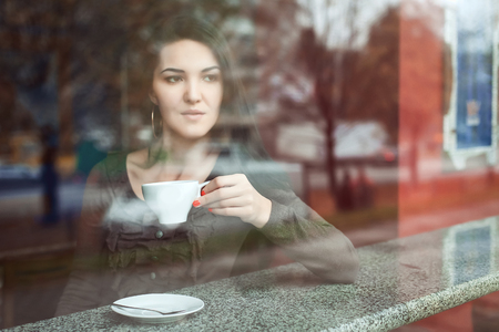 sitt: girl drinks in cafe and looks through windiw