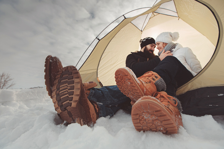 Young couple in tent during winter camping Stock Photo