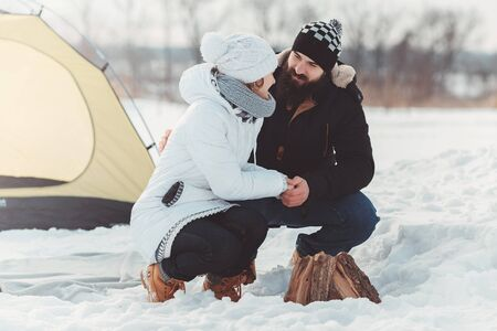 Couple hold hands near firewood over camping tent