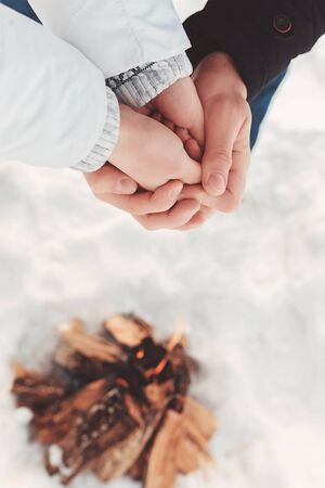 Man warms hands of a woman in his hands over snow and firewood background