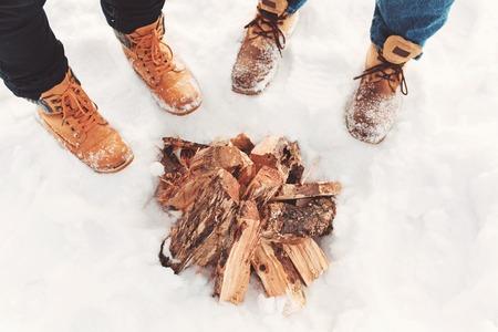 Dos personas se paran en la nieve cerca de la fogata