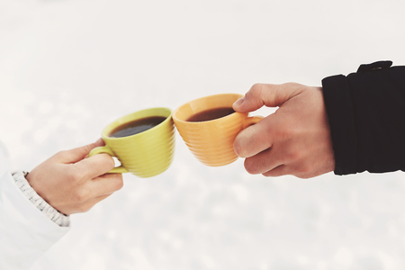 Two cups of coffee in the hands of happy couple