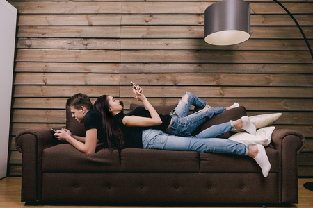 couple on couch: in love teenagers lying in bed with cell phone