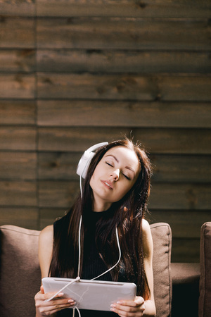 brunette woman on the sofa listening to music with closed eyes Stock Photo