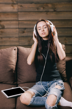 Cute beautiful brunette girl listening music with closed eyes
