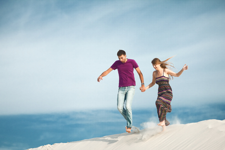 Young couple running from mountain Stock Photo