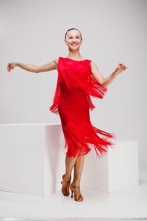 girl in red dress dancing in white studio