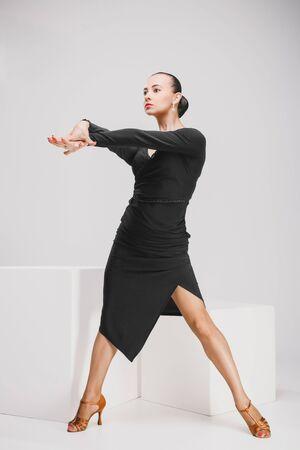 specific: woman in black dress dancing in white studio