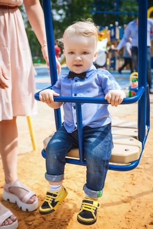 sway: little boy sitting on swing