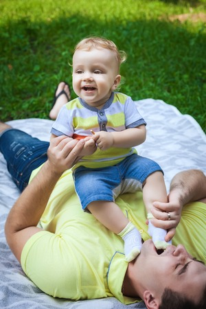 cheerful man and his son on grass Stock Photo