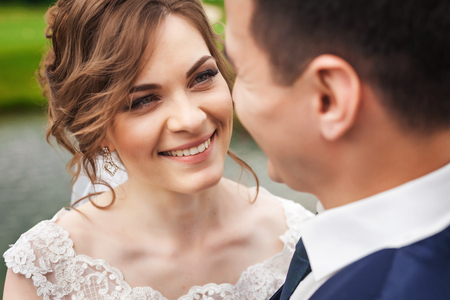 Beautiful bride and groom smiling in nature near the lake