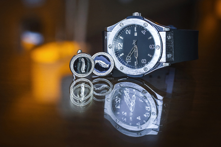 Mens watch and cufflinks on the mirrow table
