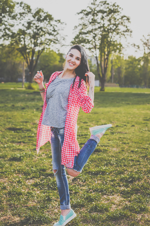 Cute hipster girl on the meadow. Looking at camera. Positive human emotion facial expression body language, concept of funny girl. Dressed in a gray t-shirt, and a shirt in a red cage