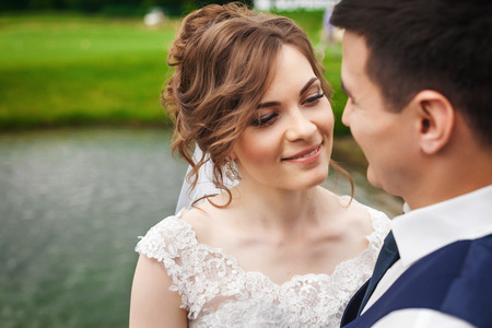 Young bride and handsome groom on wedding day. Beautiful newlyweds smiling in beautiful nature near the lake