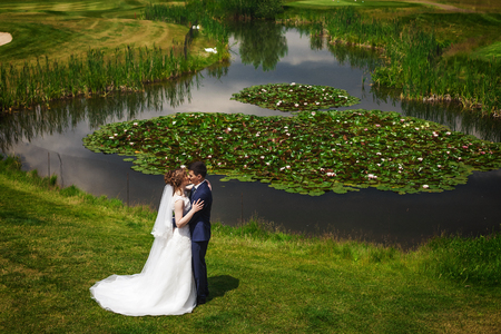 Beautiful bride and handsome groom on wedding day. Young newlyweds kissing near lake with water lilies in green nature. Concept of happy moment Stock Photo