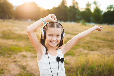 soundtrack: funny girl having fun on nature, nice child with black and silver headphones listening music and dancing