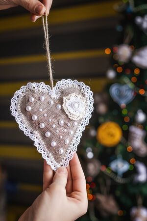 Beauty Christmas handmade sackcloth toy on blurred, sparkling and fairy tree background. concept of home Happy New Year and Xmas decor
