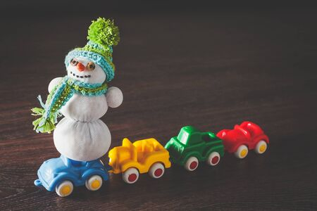 Christmas hipster snowman in green hat and scarf and color cars model on wooden background with copyspace. concept of happy new year and merry xmas gift