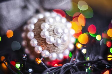 Christmas handmade twine ball and festoon on blurred, sparkling and fairy tree background. Happy New Year and Xmas theme. handmade decor