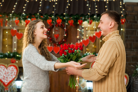 in love boyfriend and girlfriend celebrate valentines day. girl with tenderness looking at husband, smiling and enjoy flowers Stock Photo