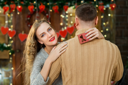 happy couple celebrate valentines day. wife with tenderness hugging husband, smiling and enjoy little present