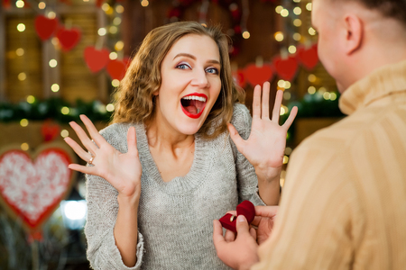 boy and girl celebrate valentines day. boy making marriage proposal, girl smiling and enjoy present with ring. Concept of happy valentines day