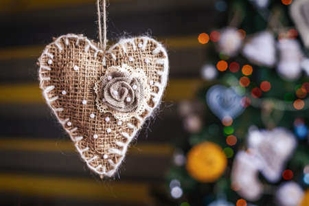 close-up Christmas handmade sackcloth herat on blurred, sparkling tree background. concept of home Happy New Year and Xmas decor