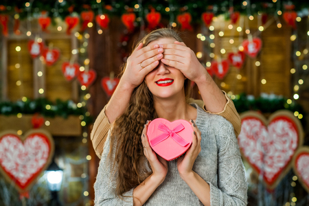 couple in love celebrate valentines day. guy making surprise on holiday to his girl and closing her eyes with hands. Concept of happy valentines day Stock Photo