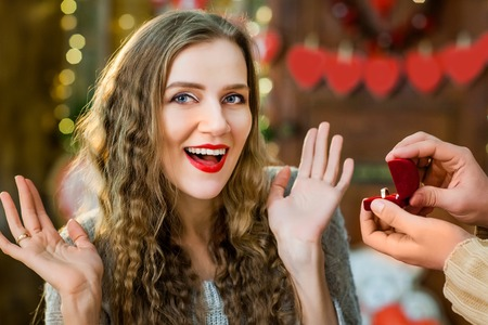 young boy and girl in love celebrate valentines day. young girl smiling and enjoy present with ring from her boyfriend Stock Photo