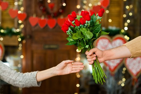 Close up shot of male hand holding flowers. Only hands with flowers over valentines day decoration Stock Photo