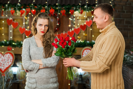 boyfriend and girlfriend celebrate valentines day. boy giving flowers to his girl. girl thinking where is her present Stock Photo