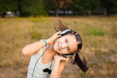 funny girl with long hair dancing outdoor, young child with black and silver headphone listening music on meadow