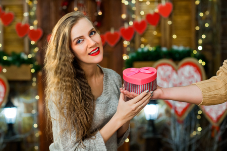 young couple in love celebrate valentines day. wife smiling and enjoy present from her husband