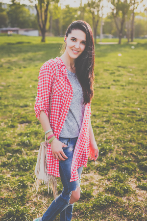 young attractive hipster girl on the meadow. Looking at camera. Positive human emotion facial expression body language, concept of funny girl. Dressed in blue ripped jeans and a shirt in a red cage