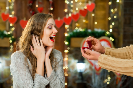 young boy and girl in love celebrate valentines day. girl smiling and enjoy present with ring from her boyfriend