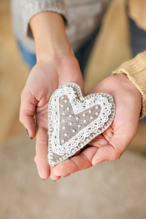 Close up shot of boy and girl hands holding heart -symbol of love valentines day.