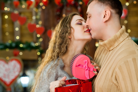 couple in love celebrate valentines day. Man making surprise on holiday and present rose box to his woman. woman enjoy present and kiss man. Concept of happy valentines day Stock Photo