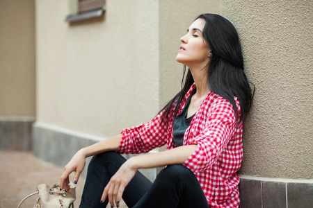 young woman resting on the ground with closen eyes, leaning against the wall. brunette female in red plaid shirt and a black trousers walking around city. Concept of modern freedom hipster human