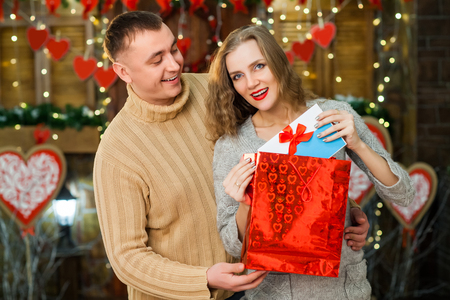 couple in love celebrate valentines day. boy giving present in red box to his pretty girl. Girl enjoy present. Concept of happy valentines day