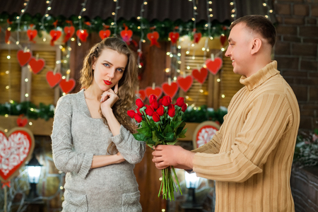 in love boyfriend and girlfriend celebrate valentines day. boy giving flowers to his girl. girl thinking where is her present Stock Photo