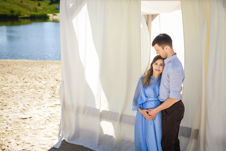 future mother with curly long hair in beautiful blue dress and handsome father hugging near light alcove on beach, happy family concept