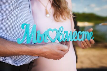 future mom with curly long hair in beautiful pink dress and handsome dad hugging in wooden terrace, holding blue title we are together close up, happy family concept